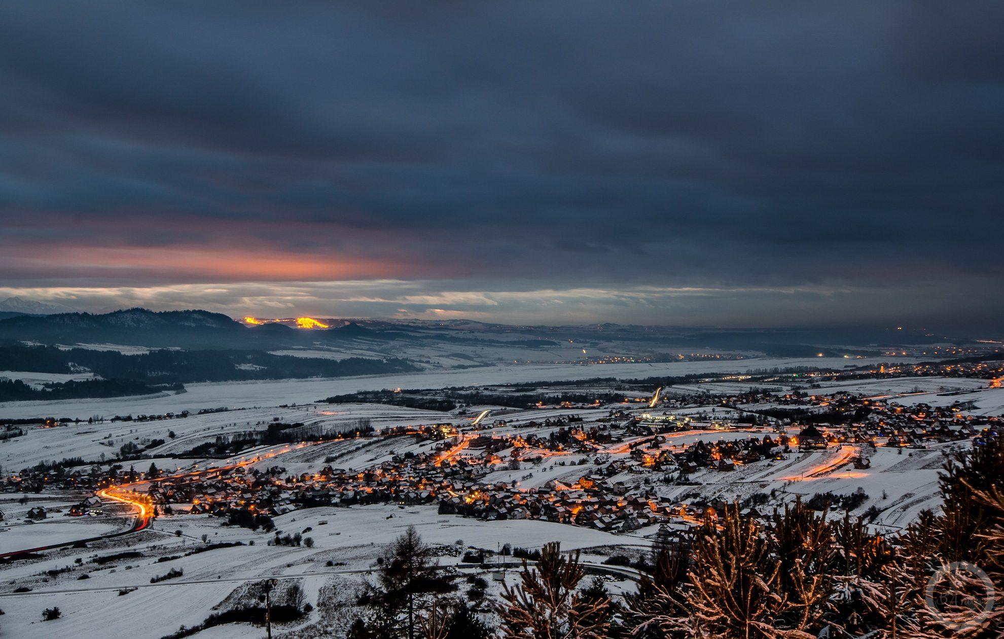 Widok naKluszkowce pozmroku. Widoczne światła miejscowości iresztki zachodzacego słońca. Pieniny