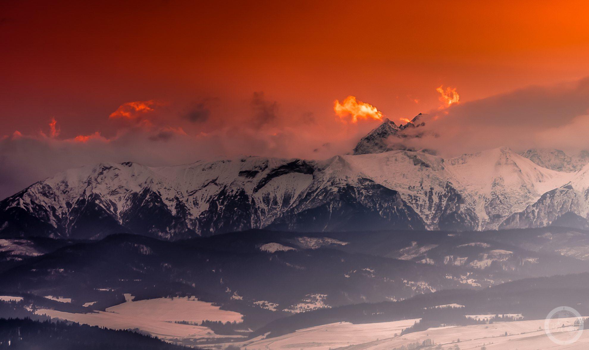 """Widok naTatry natle """"podpalonego"""" zachodem słońca nieba. Widoczne ośnieżone szczyty gór."""