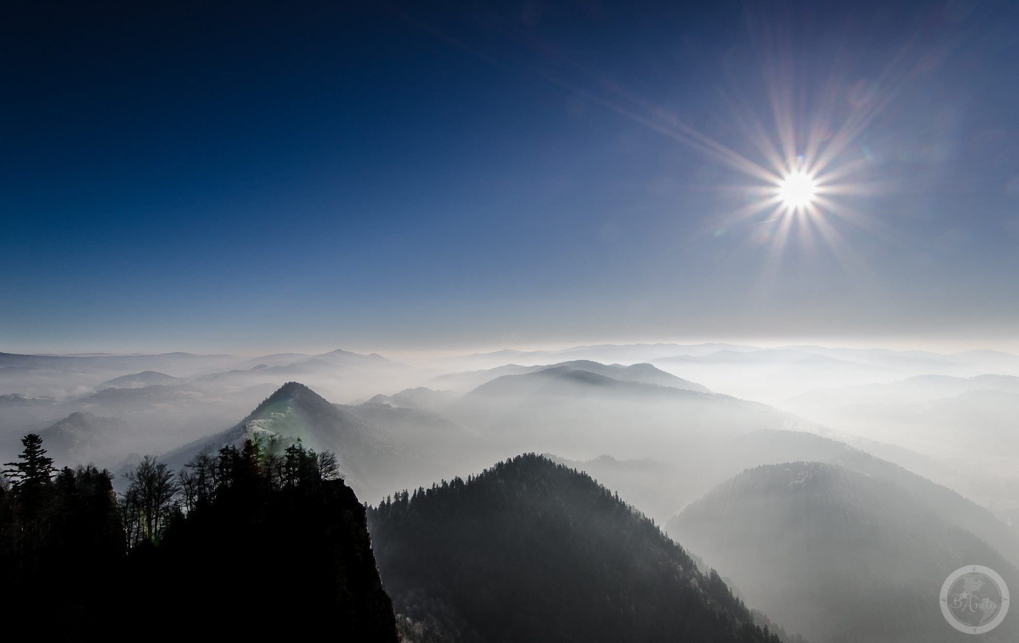 Widok zTrzech Koron nazamglony Beskid Wyspowy. Czyste niebo iszczyty wyłaniające się zmgieł spowijających doliny