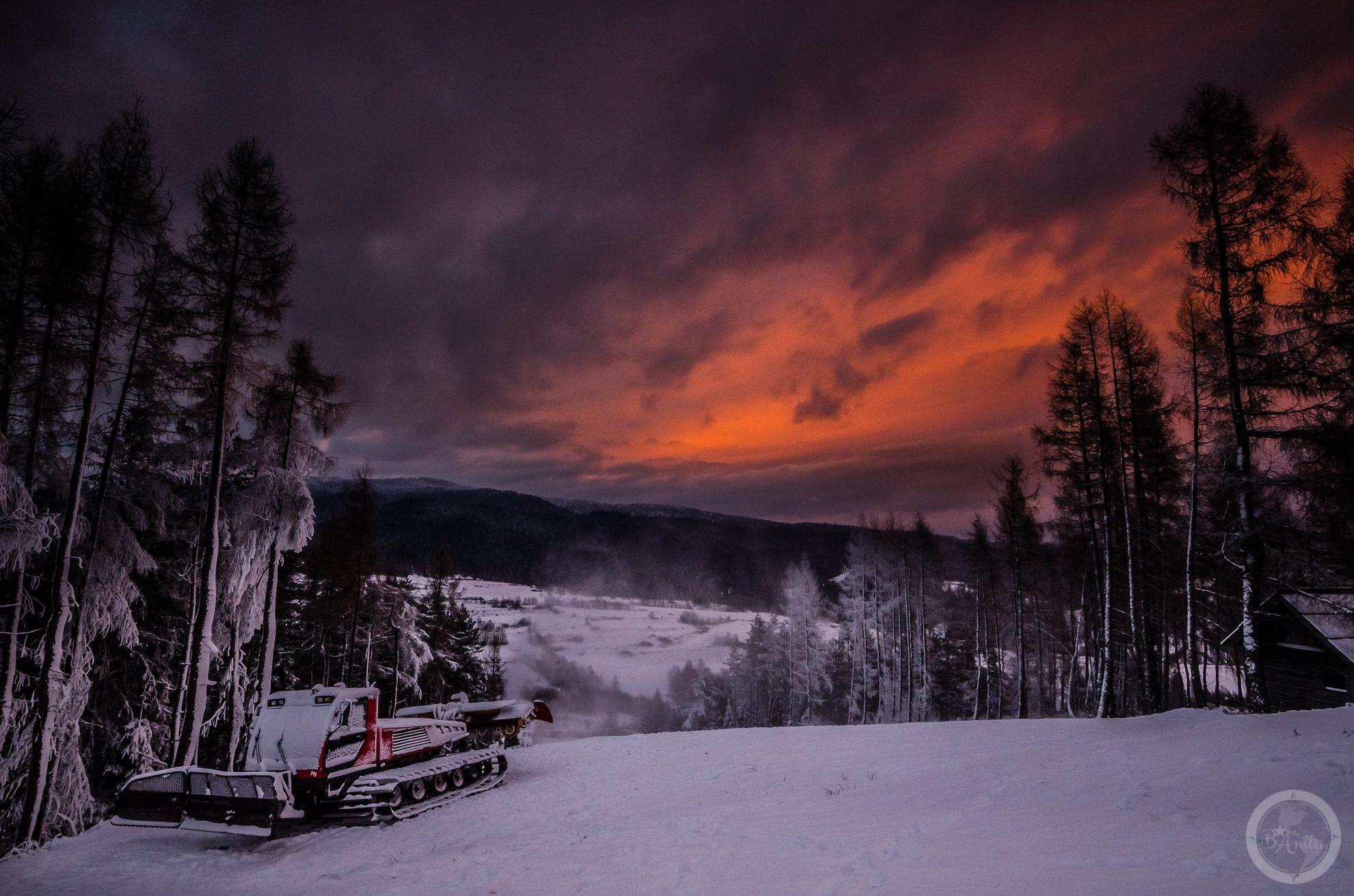 Widok zgóy Wdżar. Wlewym rogu widoczny ratrak. Nadszczytami pokolorowane zachodzacym słońcem chmury.