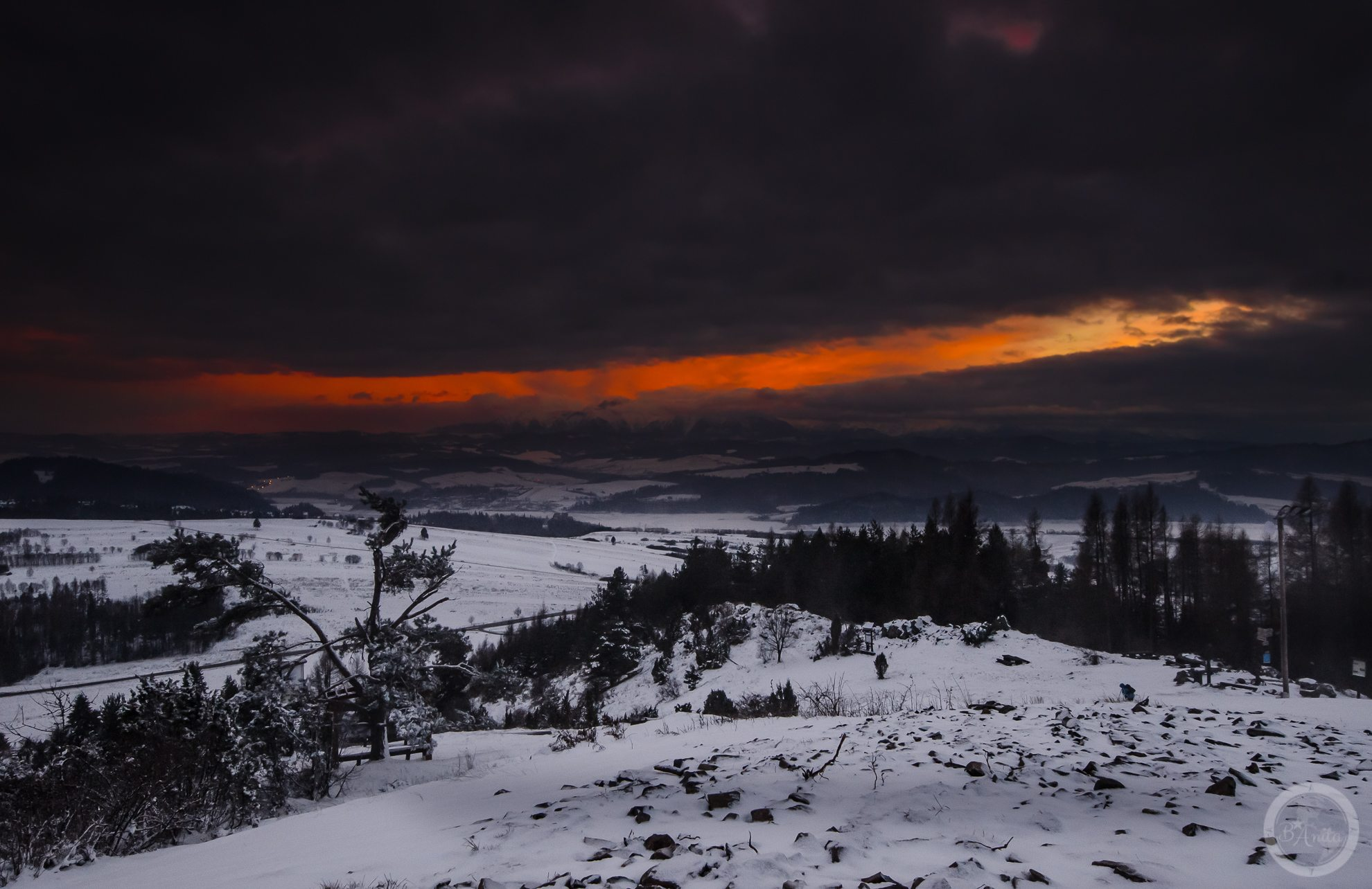 Zachód słońca widziany zGóry Wdżar (766, 767 m), szczytu wpaśmie łączącym Lubań zPieninami, pomiędzy przełęczami Drzyślawa iSnozka. Widoczna szczelina wchmurach, przez którą wdzira się ogień zachodzącego słońca.