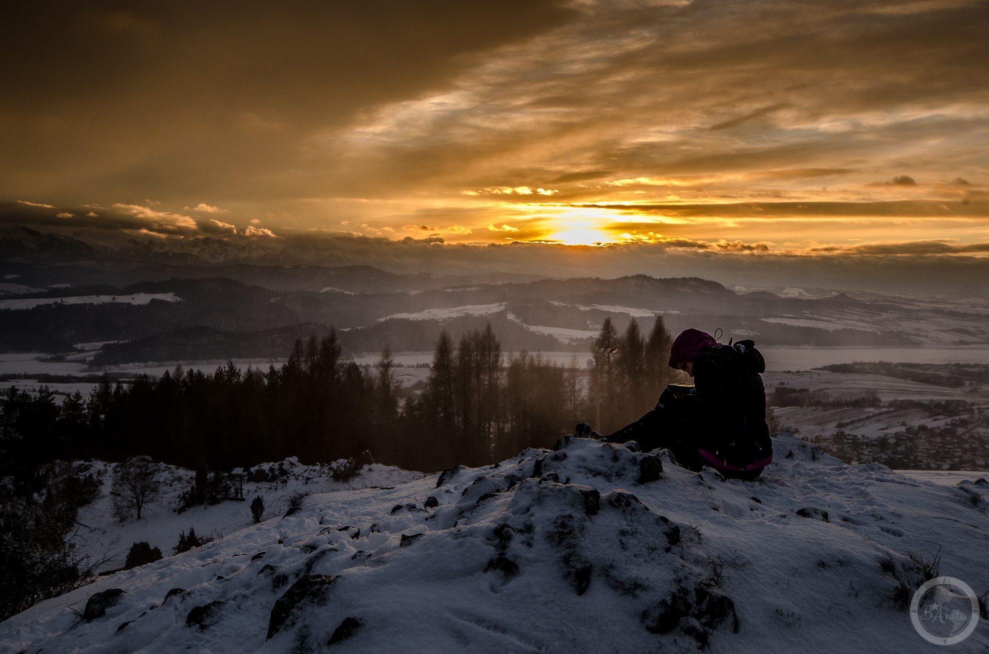 Turysta siedzący naośnierzonym pagórku. Zachód słońca widziany zGóry Wdżar (766, 767 m), szczytu wpaśmie łączącym Lubań zPieninami, pomiędzy przełęczami Drzyślawa iSnozka.