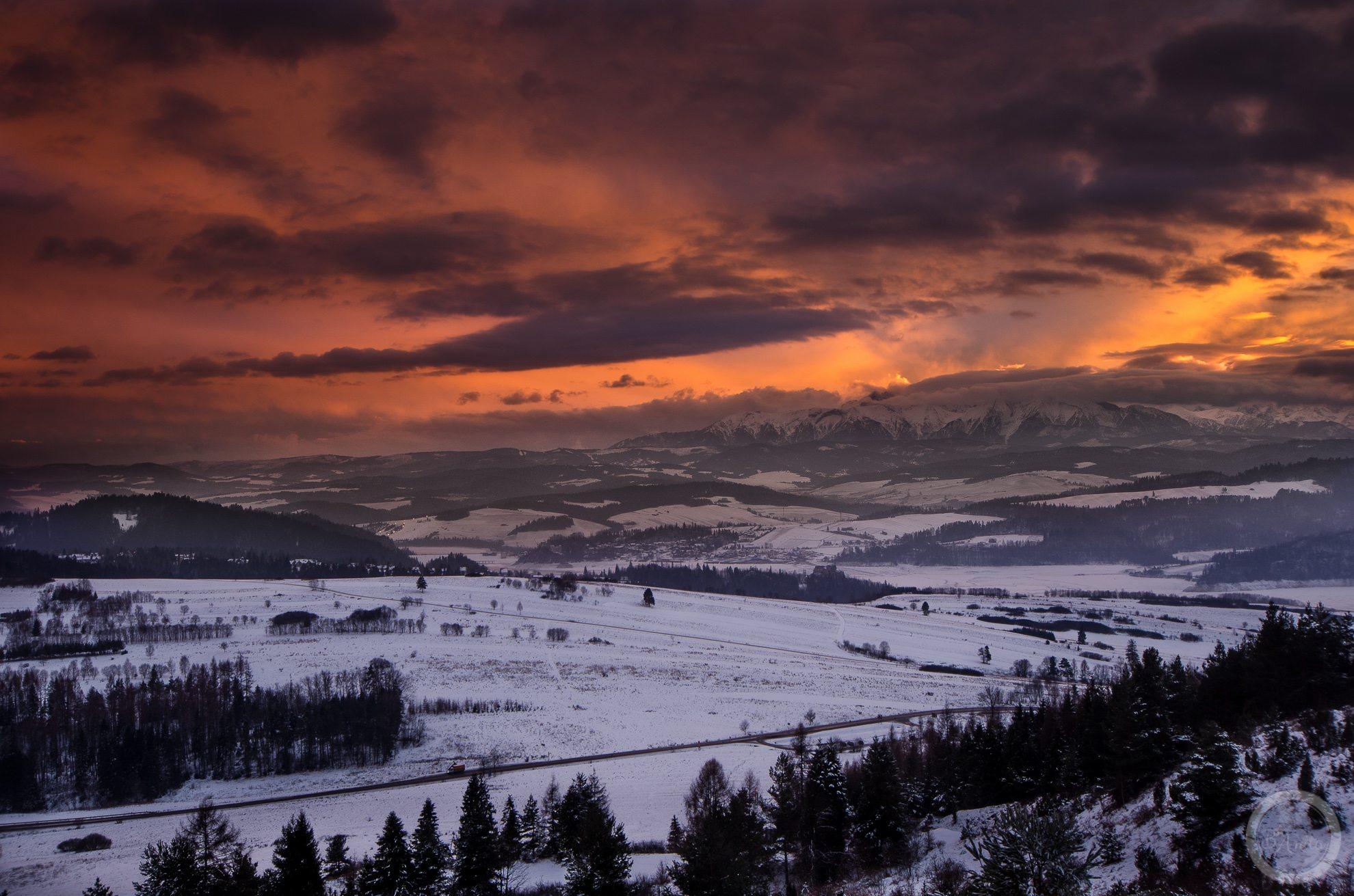 Wieczorny widok zGóry Wdżar (766, 767 m), szczytu wpaśmie łączącym Lubań zPieninami, pomiędzy przełęczami Drzyślawa iSnozka. Woddali widoczne Tatry oświetlone zachodzącym słońcem