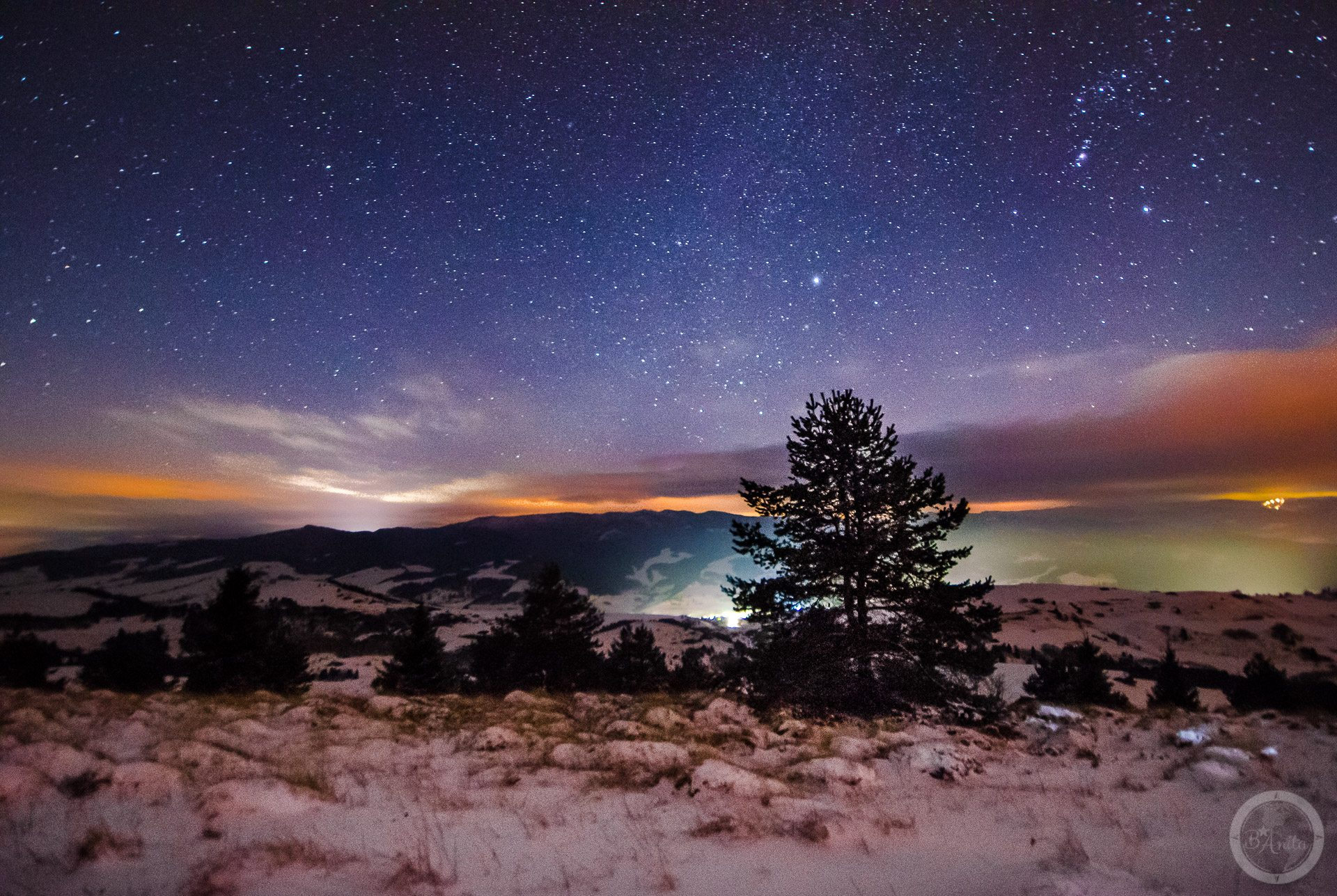 Nocne zdjęcie rozgwieżdżone nieba wykonane naszczycie góry. Wysoki Wierch, Małe pieniny Wdolinach widać światła miasteczek.