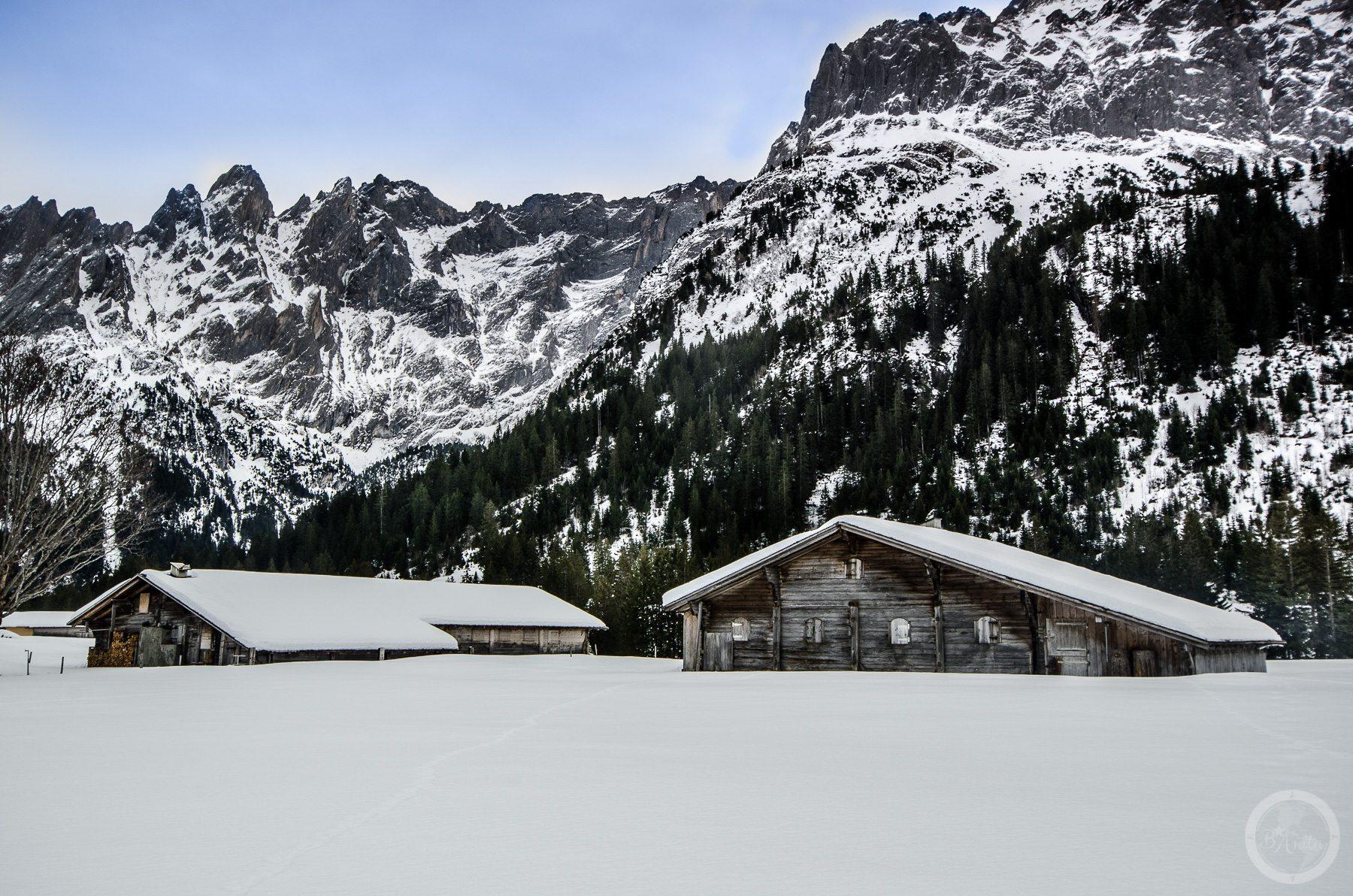 Drewniane ośnieżone chaty u podnóża skalistych gór. Schwarzwaldalp, Szwajcaria